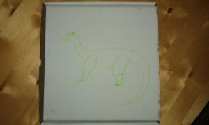 Auf dem Karton ist mit grünem Filzstift etwas gemalt, das durchaus als Brontosaurier durchgehen könnte.