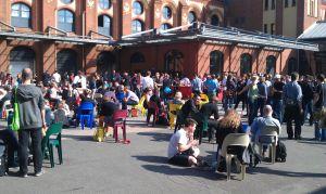 Der sonnenüberflutete Innenhofder Station mit hunderten Teilnehmern auf Plastikstühlen