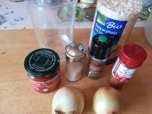 (v.l.n.r.) Tomatenmark, 100 ml Wasser, Salz, Pfeffer, 100 g Reiswaffeln, Paprikapulver und zwei Zwiebeln