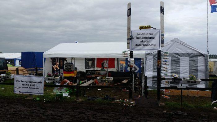 """Ein typisches Camp beim Wacken Open Air: Pavillons mit Zaun davor und Schildern auf denen etwa """"Institut zur bekämpfung akuter Unterhopfung"""" steht."""