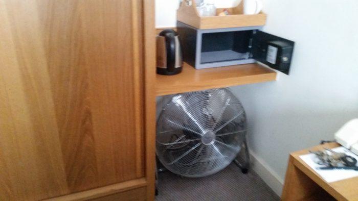 Ein großer Ventilator steht unter einer Ablage neben meinem Bett im Hotel.