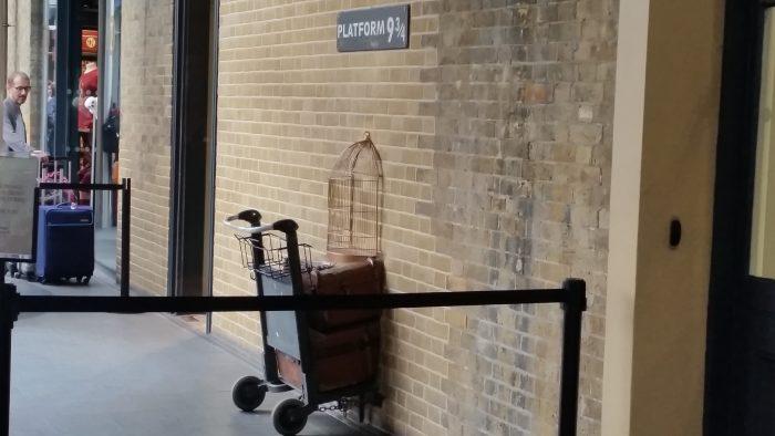 """In einer Wand mit einem Schild """"Platform 9 3/4"""" ist ein Gepäckwagen halb in der Wand verschwunden"""