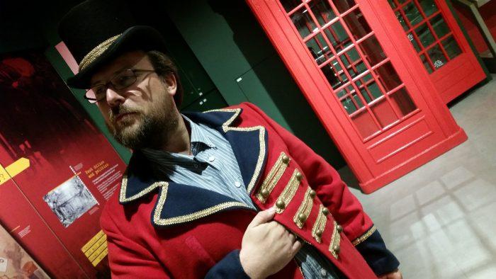 Ich stehe mit Zylinder und einem roten Jackett in alberner Pose im Museum.