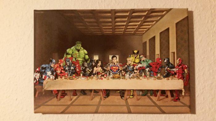 13 Comichelden von DC und Marvel sind wie zum letzten Abendmahl arrangiert.