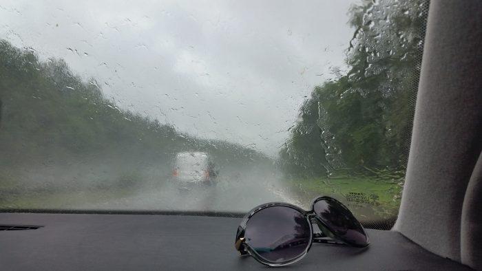 Eine Sonnenbrille liegt auf der Ablage eines Autos auf der Beifahrerseite, die Windschutzscheibe ist voller Regenwasser.