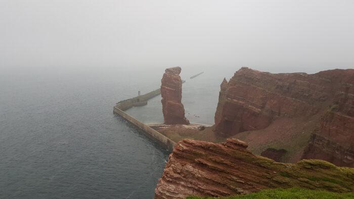 Der Blick vom Vogelfelsen auf die Lange Anna und den Wellenbrecher. Durch den Nebel gibt es im Hintergrund keine erkennbare Horizontlinie.