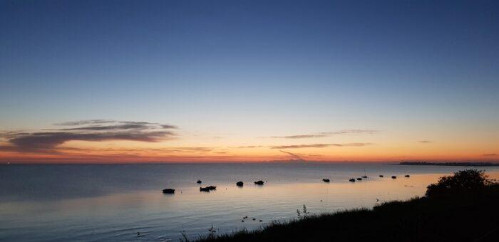Das Bild zeigt die Kieler Außenförde von der Steilküste in Stein aus. Die Sonne geht bald auf und im Vordergrund liegen einige Boote im Wasser vor Anker.