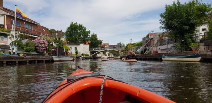Das Bild zeigt die Friedrichstädter Altstadt von meinem Leih-Kajak aus. Rechts und links der Gracht liegen die Boote der Anwohner, an den Anlegern sind Blumen gepflanzt und die Fahne Nordfrieslands weht in einem der Gärten.