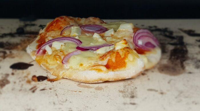 Das Bild zeigt eine Mini-Pizza auf unserem Pizzastein im Grill.