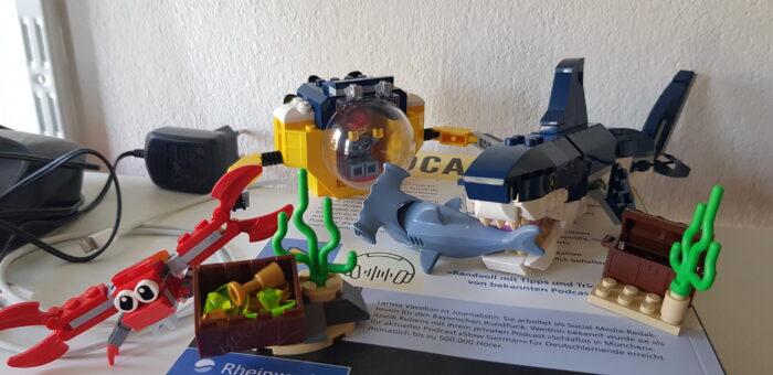 Das Bild zeigt zwei miteinander kombinierte Legosets. In der dargestellten Szene beobachtet ein Mensch in einem Forschungsuboot, wie ein Megalodon einen Hammerhai frisst, während im Vordergrund ein riesiger Krebs die Flucht ergreift.