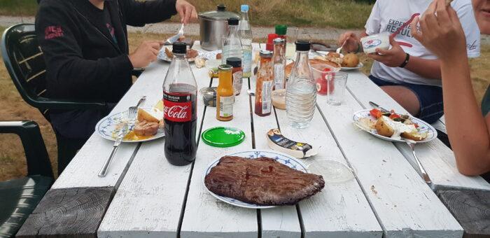Das Bild zeigt einen Tisch im Landhaus-Stil auf dem Getränke, Grillsaucen und diverses Essen steht. Im Vordergrund steht ein Teller, der komplett von einem Stück Flanksteak eingenommen wird.