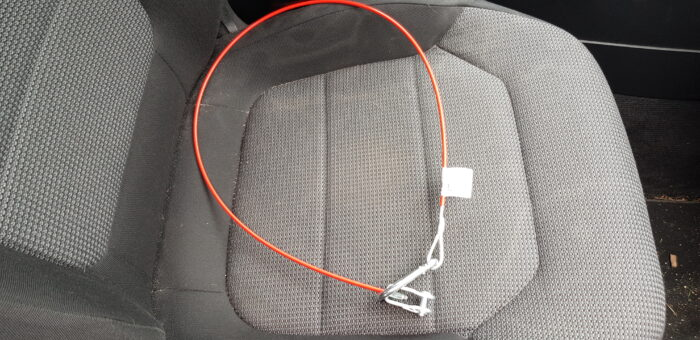 Auf dem Beifahrersitz unseres Autos liegt ein neues Abreißseil. Es ist rot und ungefähr 70 cm lang. Der Karabinerhaken am einen und die Sollbruchstelle am anderen Ende sind in eine Schleife gelegt. An dem Ende mit dem Karabinerhaken sieht man noch das Preisschild.
