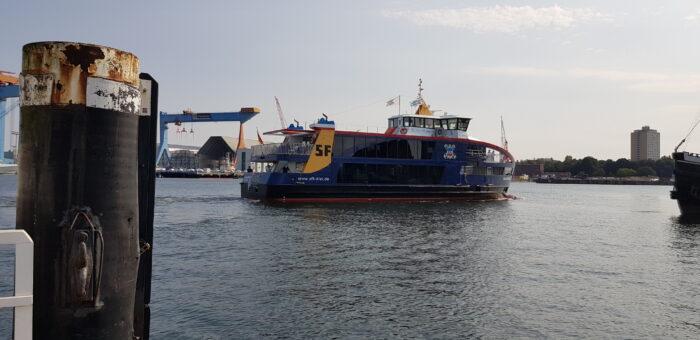 Das Bild zeigt die MS Gaarden auf Höhe des Anlegers Seegarten. Im Vordergrund ist ein Poller zu sehen, m Hintergrund die Portalkräne der German Naval Yards-Werft.