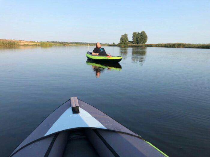Im Vordergrund ist die Spitze von Gesches Kayak zu sehen, in der Bildmitte im Hintergrund lehne ich mich in meinem Kayal zurück und genieße die Abendsonne auf der Treene. Der Wasseroberfläche ist fast völlig glatt.