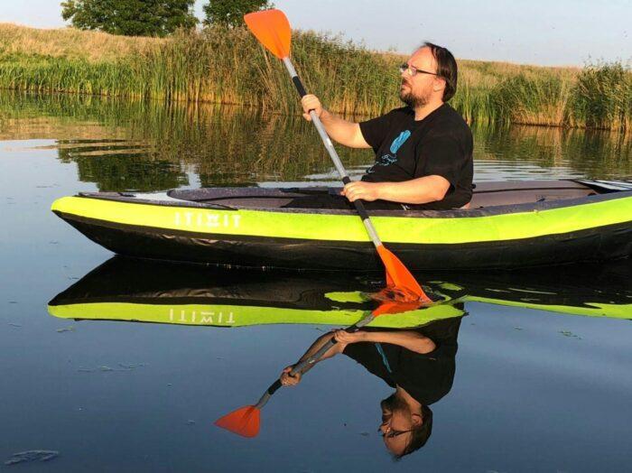 Das Bild zeigt mich, wie ich in meinem Kayak von rechts nach links an der Kamera vorbeipaddele, ein Paddelblatt ist dabei im Wasser, eines in der Luft. Das Wasser ist so glatt, dass ich mich darin spiegele.