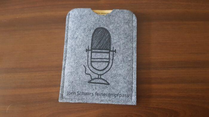 """Eine graue Filzmappe liegt auf einer dunklen Holzplatte. Aufgedruckt sind ein stilisiertes Mikrofon und der Schriftzug """"Jörn Schaars feiner Impfpass"""". Am oberen Ende ist eine kleine Aussparung im Stoff, durch die man den Impfpass greifen kann."""